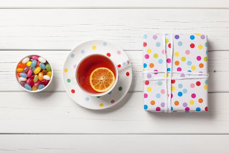 Geschenkbox, Tasse Tee und bunte Süßigkeiten auf weißem hölzernem backgr stockfotografie