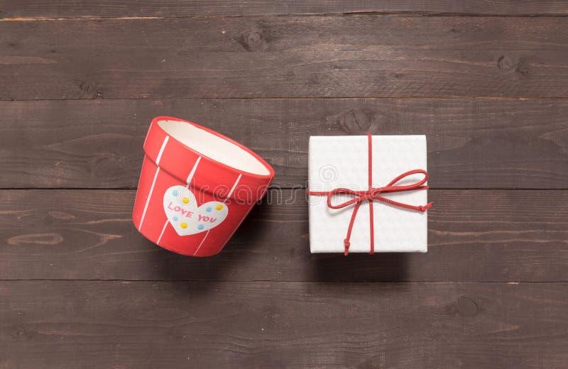 Geschenkbox- und Blumentopf sind auf dem hölzernen Hintergrund mit leerem lizenzfreie stockbilder