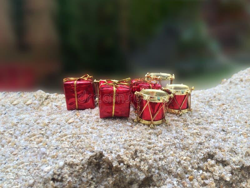 Geschenkbox- und Trommeldekoration mit Goldband auf dem Sand stockbild