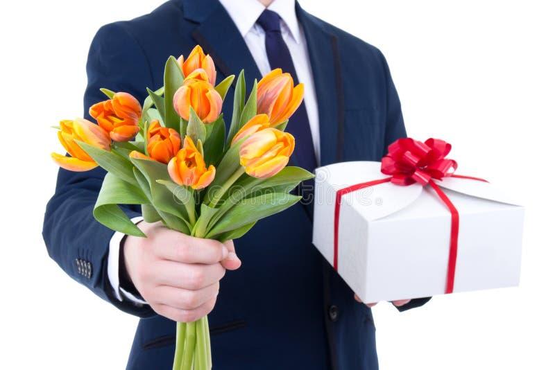 Geschenkbox und Tulpe blüht in den männlichen Händen, die auf Weiß lokalisiert werden stockfotos