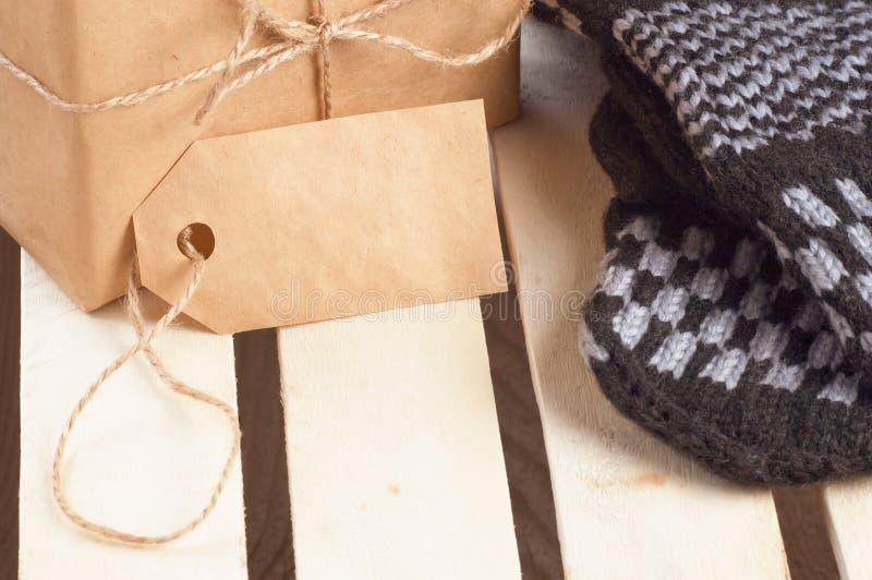 Geschenkbox verpackte braunes Papier und Schnur mit leerem Tag und handgemachte Handschuhe in der Nähe auf hölzerner Gitterplatte stockbilder