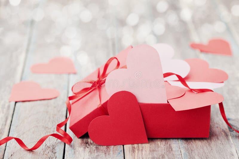 Geschenkbox voll Herzen auf hölzernem Hintergrund für Heilig-Valentinsgruß-Tag lizenzfreies stockbild