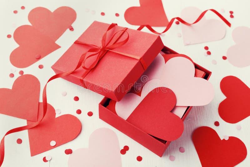 Geschenkbox voll Herzen auf weißem Hintergrund für Heilig-Valentinsgruß-Tag stockfotografie