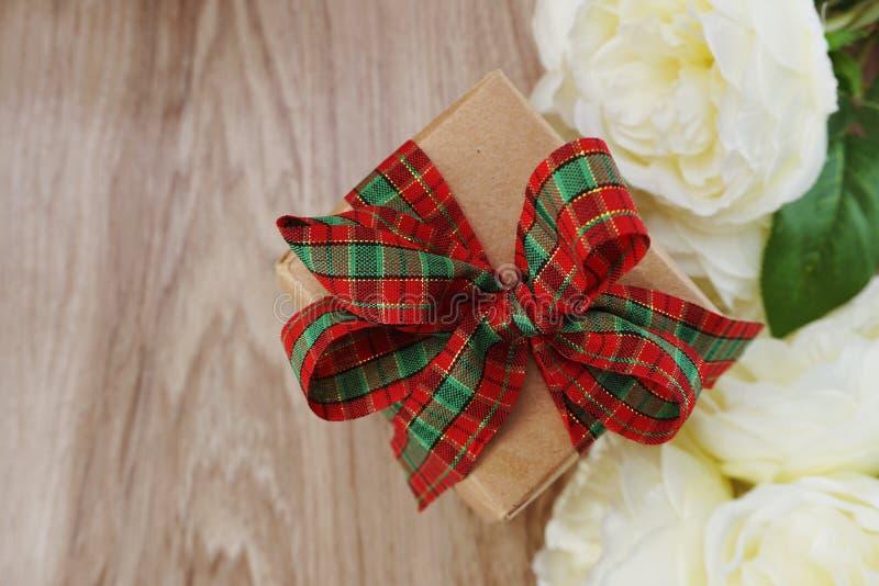 Geschenkbox vorhanden mit rotem Band- und Blumenblumenstrauß auf hölzernem Hintergrund des Raumes lizenzfreies stockfoto