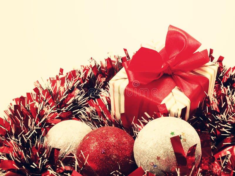 Geschenkbox vorhanden mit roten Banddekorationen mit roter und weißer Lamettaweihnachtshintergrundweinlese lizenzfreies stockbild
