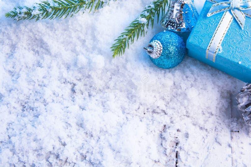 Geschenkboxbälle, Kiefernkegel und grüne Niederlassung auf Schnee stockfotografie