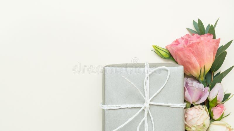 Geschenkboxblumen-Elfenbeinhintergrund der Frauen anwesender stockfoto