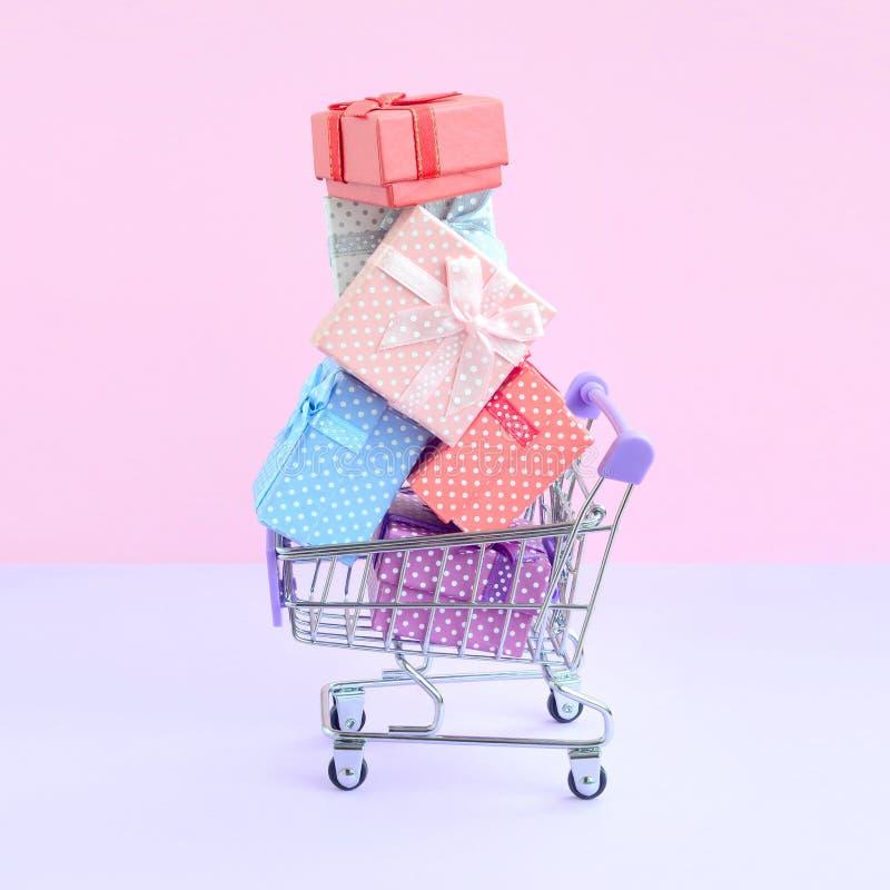 Geschenkboxen für Winterurlaube im Supermarkteinkaufswagen lizenzfreie stockbilder