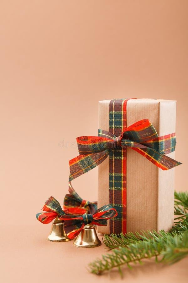 Geschenkboxen im grauen Packpapier, Weihnachtsglocken, Kiefer auf beige Hintergrund lizenzfreies stockbild