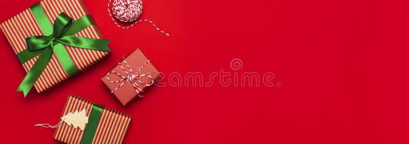 Geschenkboxen mit grünem Band auf roter Draufsicht-Ebenenlage des Hintergrundes Feiertagskonzept, neues Jahr oder Weihnachtsgesch stockbilder
