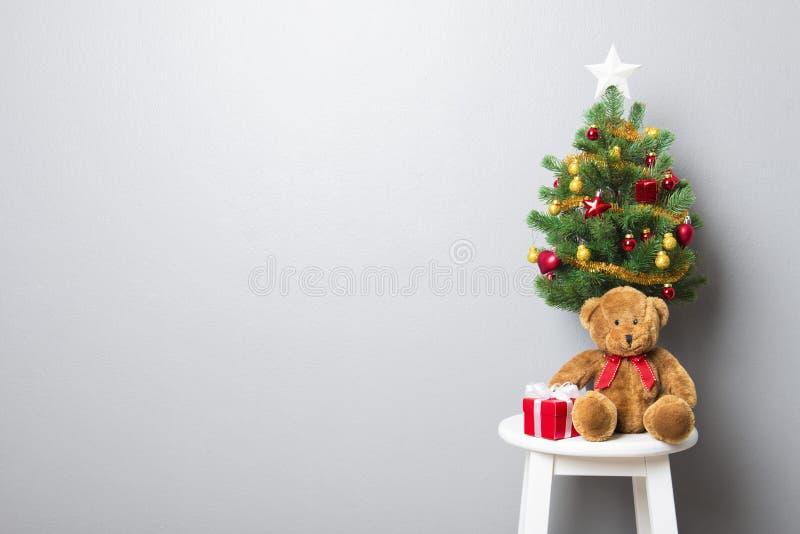 Geschenkboxen, Teddybär und kleiner verzierter Weihnachtsbaum auf sto stockbild