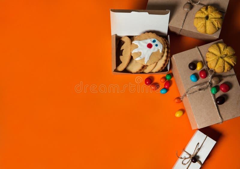 Geschenkdosen, hausgemachte Kekse mit gruseligen Gespenstern und Fledermäusen, bunte Köstlichkeiten auf orangefarbenem Hintergrun lizenzfreies stockbild