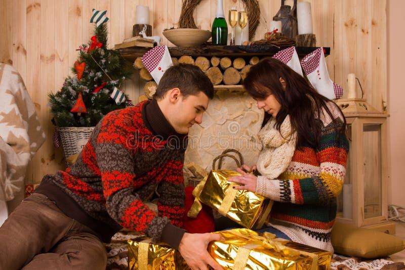 Geschenke Öffnung des jungen Mannes und der Frau Weihnachts stockbilder