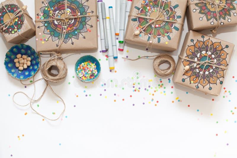 Geschenke eingewickelt im Kraftpapier Auf Kästen gemaltes Mandalamuster stockbild