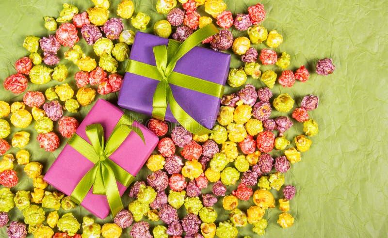 Geschenke und Bonbons Feierlicher Hintergrund Mehrfarbiges Popcorn und Geschenkboxen lizenzfreies stockfoto