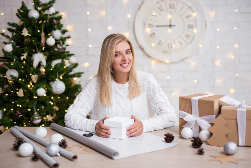 Geschenke Verpackung der jungen Frau Weihnachtszu hause stockbild