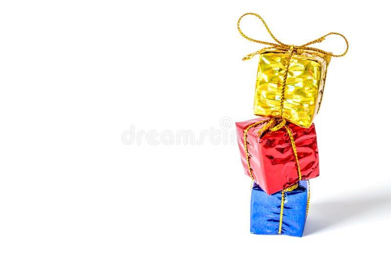 Geschenkkästen in einem mehrfarbigen Paket, das mit einem Bogen verbunden wird, stehen in einer lokalisierten Spaltennahaufnahme stockfotografie