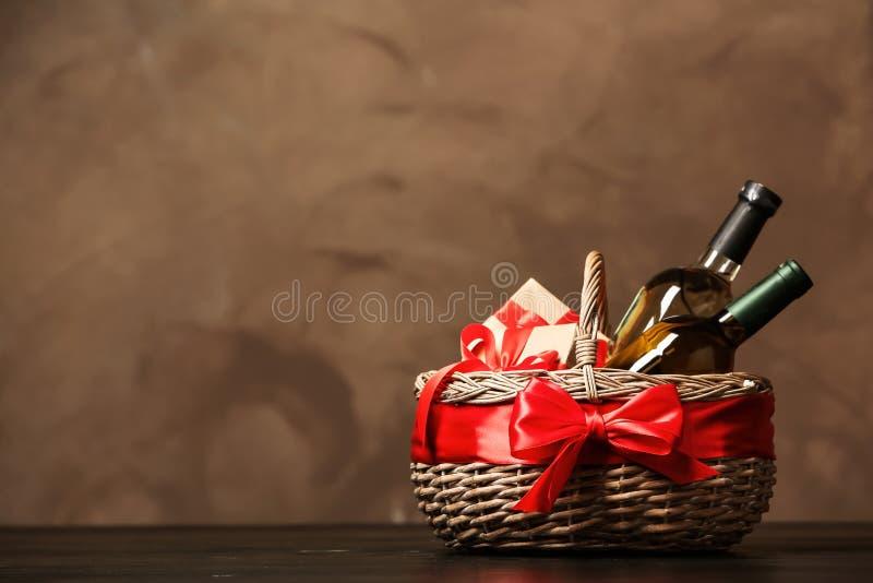 Geschenkkorb mit Flaschen Wein auf dunklem Hintergrund stockbild
