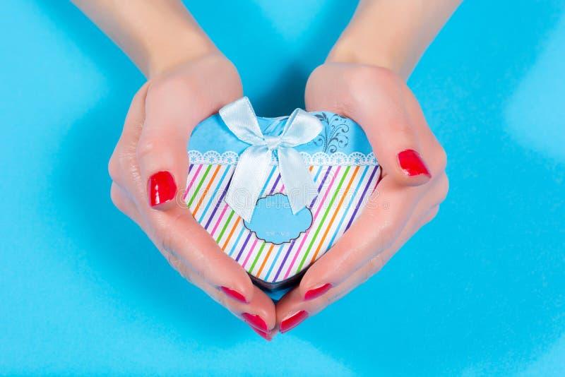 Geschenkschachtel in Herzform auf blauem Hintergrund im Studio stockbild