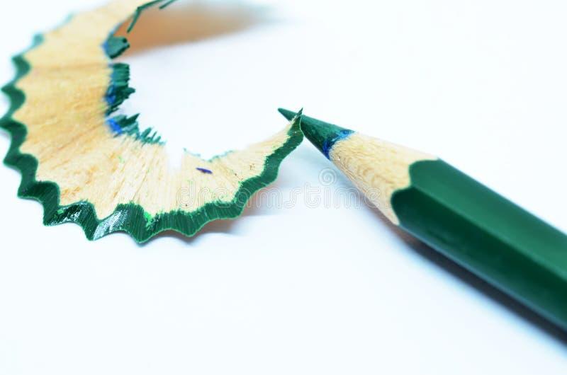 Gescherpt groen kleurenpotlood en schaafsel stock fotografie