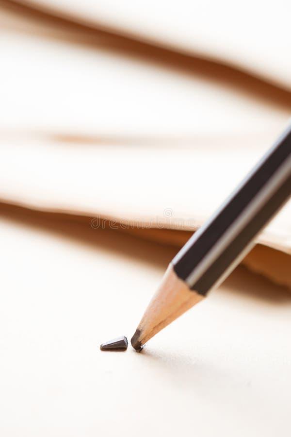 gescherpt potlood over een leeg oud blad van document met gebroken t stock foto's