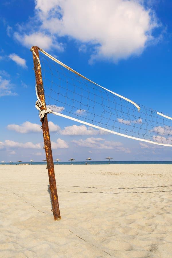 Gescheurd volleyball netto op het strand met bewolkte blauwe hemel en geel zand stock foto's