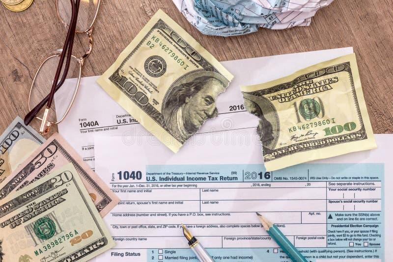 Gescheurde dollar op de belastingsvorm van de V.S. 1040 royalty-vrije stock afbeeldingen