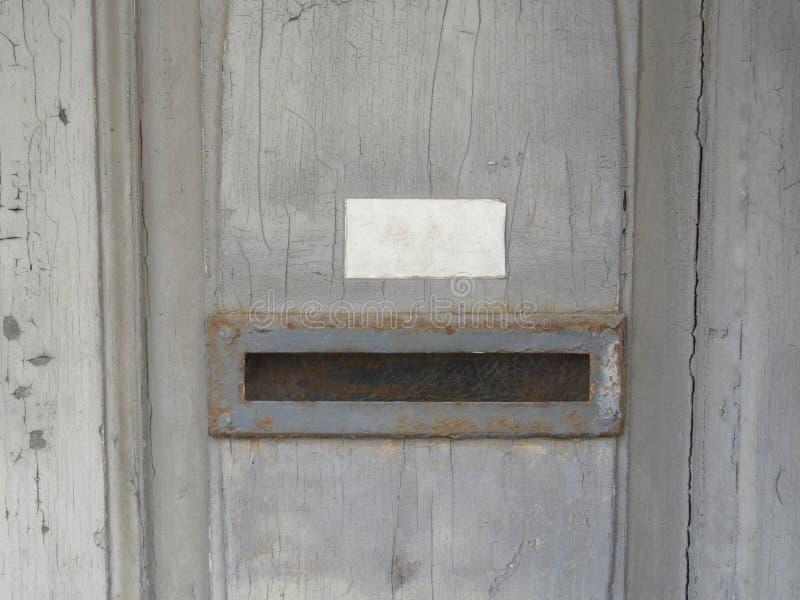 Gescheurde en gedeeltelijk afgebladderde lagen van verf op een oude houten deur met duidelijke barsten, brievenbusgroef royalty-vrije stock afbeeldingen