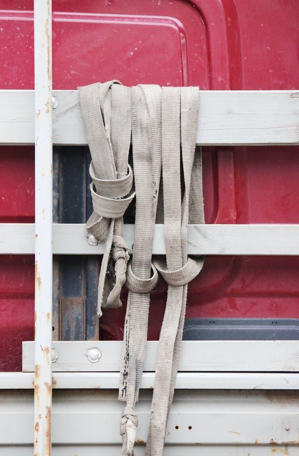 gescheurde grijze nylon slingers die aan boord van de vrachtwagen hangen royalty-vrije stock fotografie