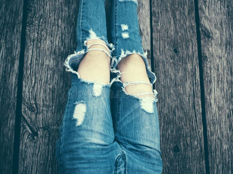 Gescheurde jeans vrouwelijke voeten De benen van de maniervrouw in jeans en schoenen op houten vloer Het meisje is het zitten, dr royalty-vrije stock afbeeldingen