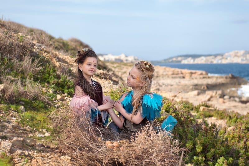 Geschichte von Märchen über zwei Vogelmädchen Brunette und blondes Sitzen in einem enormen Nest mit Ostereiern stockfotos