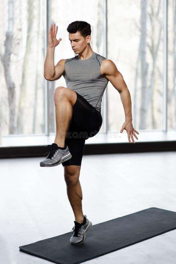 Geschikt, atletisch mannelijk model in sportkleding die die sterkteoefening met knie omhoog in gymnastiek doen, op een grote vens stock afbeelding