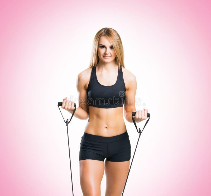 Geschikt, gezond en sportief meisje in sportkleding die de roze achtergrond van de expanderoefening doen royalty-vrije stock foto's