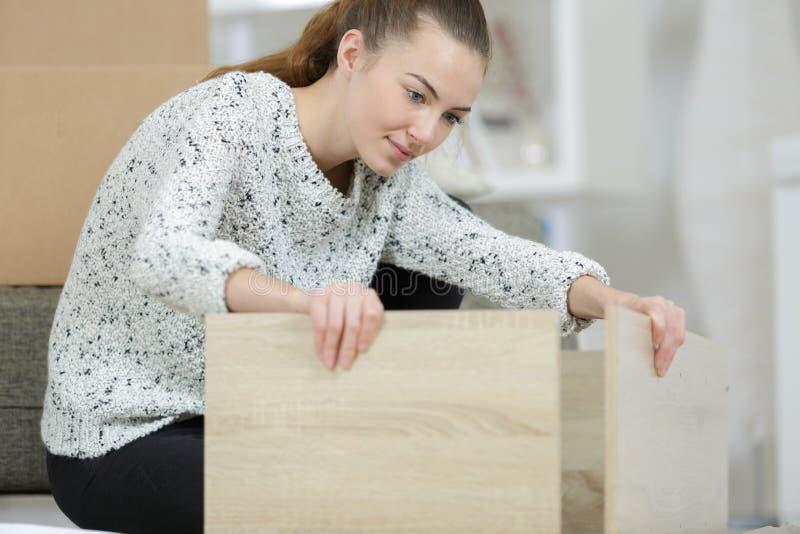 Geschikt jong dame het assembleren flatpack meubilair stock foto's