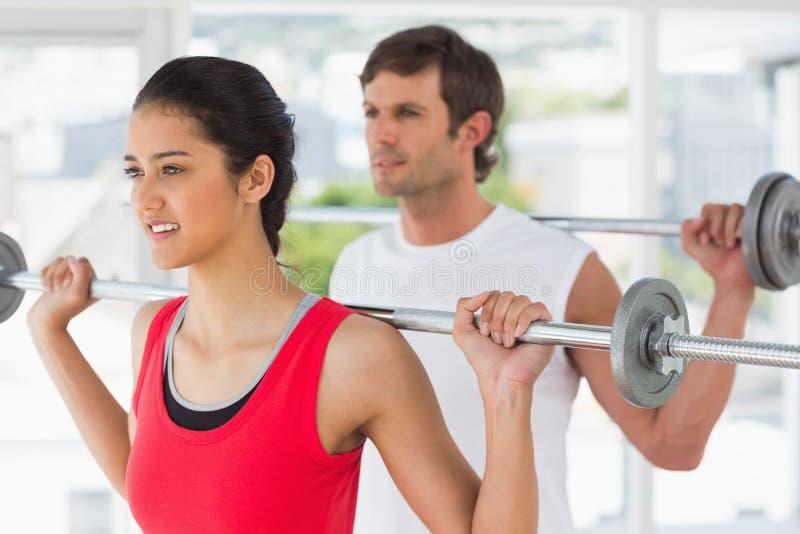 Geschikt jong paar die barbells in gymnastiek opheffen stock afbeelding