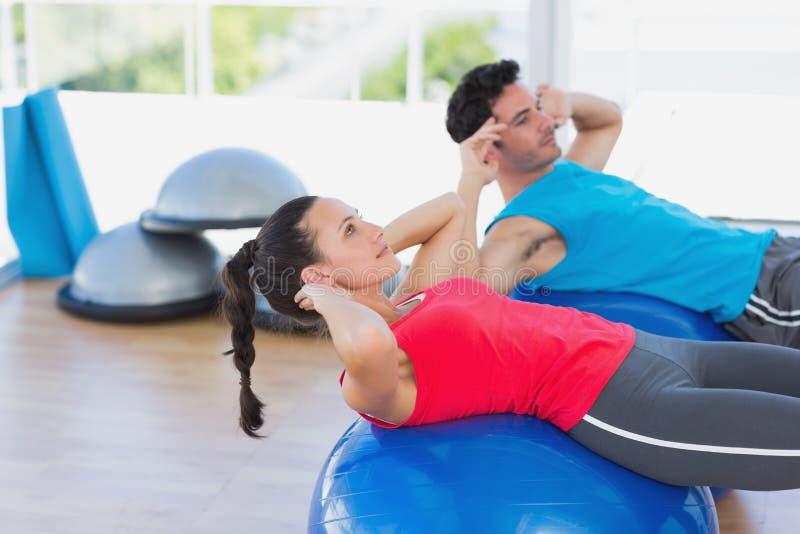 Geschikt jong paar die op geschiktheidsballen bij gymnastiek uitoefenen royalty-vrije stock foto's