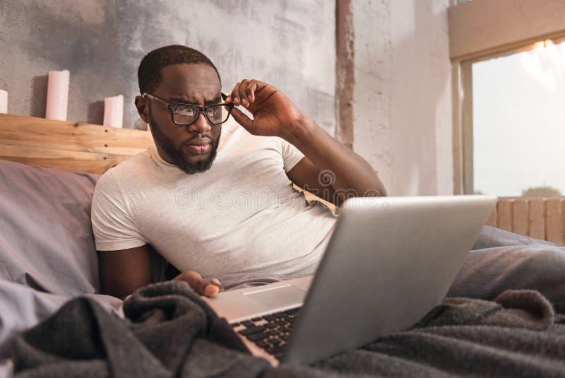 Geschikt jonge Afrikaanse Amerikaanse mens die thuis werken royalty-vrije stock afbeelding