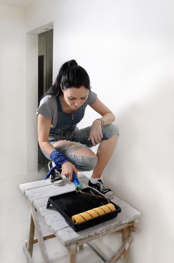 Geschikt jonge vrouw die een muur schilderen royalty-vrije stock afbeeldingen
