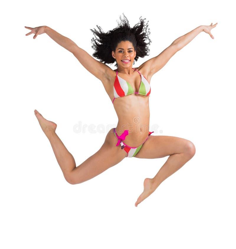 Geschikt meisje in bikini die en bij camera springen glimlachen royalty-vrije stock afbeeldingen