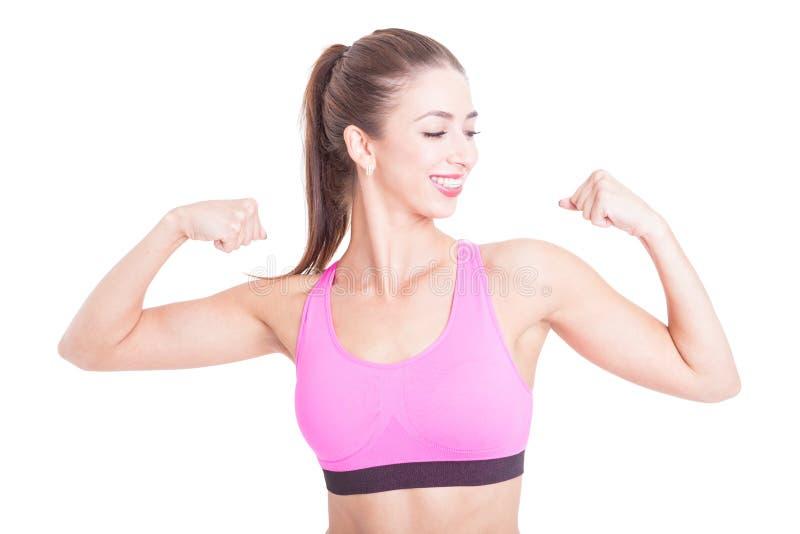Geschikt meisje die en haar bicepsen glimlachen tonen royalty-vrije stock afbeeldingen
