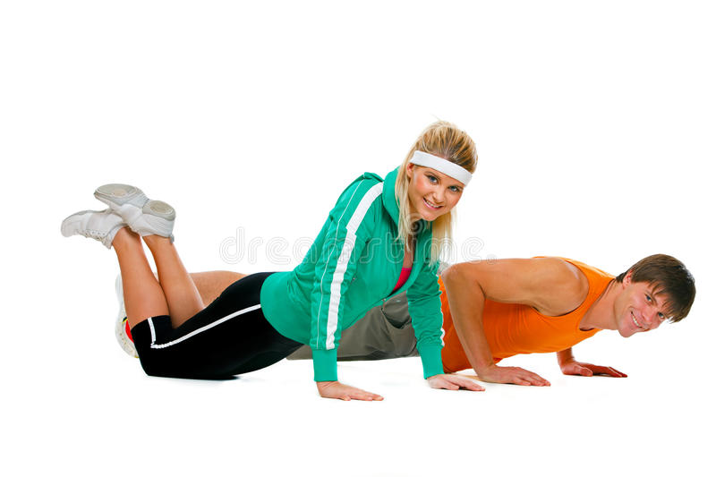 Geschikt meisje en mannelijke atleet die opdrukoefeninguitoefenaar maken stock foto