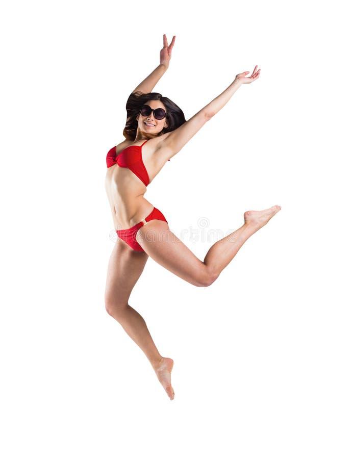 Geschikt meisje in rode en bikini die glimlachen springen stock afbeelding