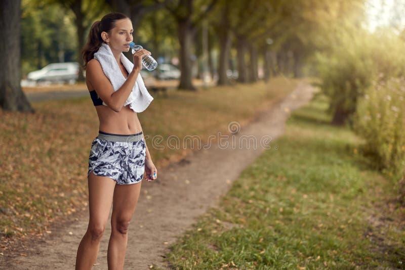 Geschikt sportief vrouwen drinkwater van een plastic fles royalty-vrije stock fotografie