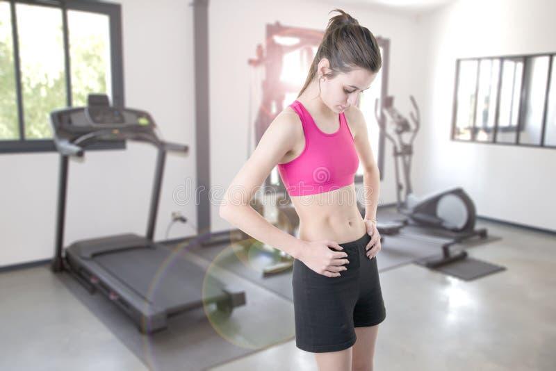 Geschikt vrij slank meisje in privé gymnastiek thuis binnenland met het verschillende materiaal van de sportoefening stock foto