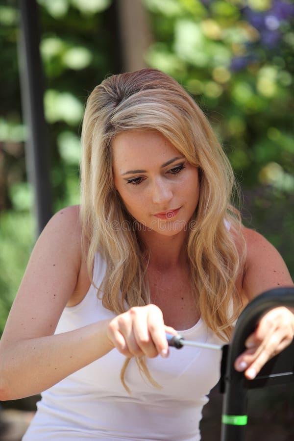 Geschikt vrouw die reparaties met een schroevedraaier doen stock afbeeldingen