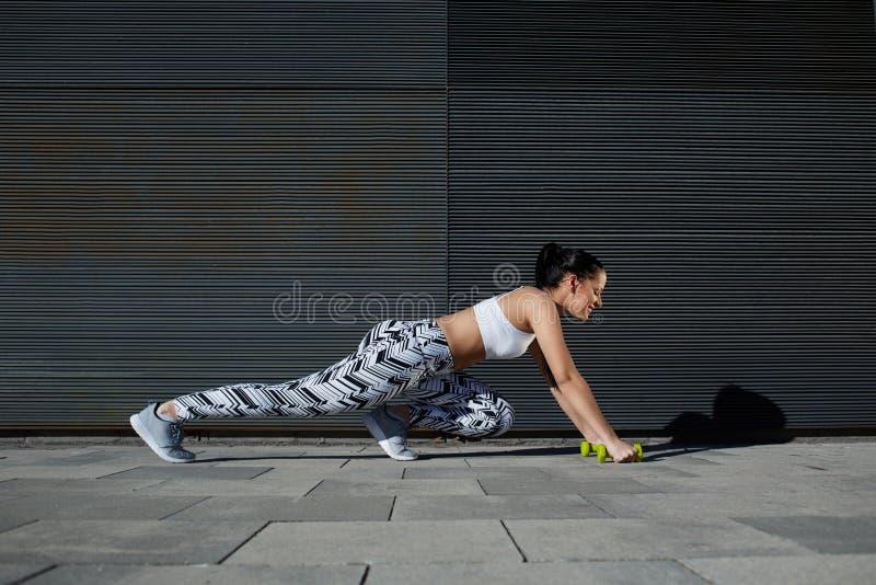 Geschikt wijfje in trainingtoestel die opdrukoefeningen op zwarte achtergrond in openlucht doen stock afbeeldingen