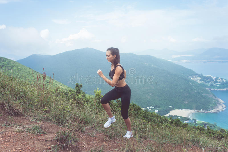 Geschikt wijfjes jogger uitoefenende, lopende helling met overzees en bergen op achtergrond royalty-vrije stock fotografie