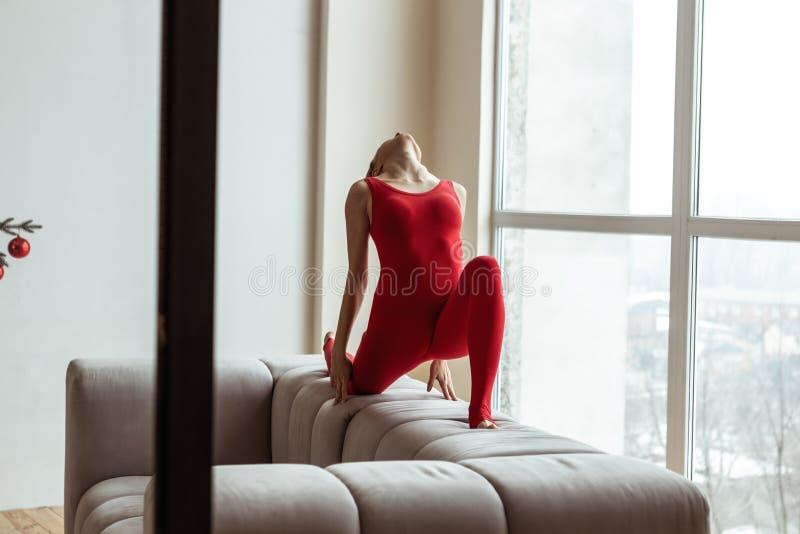 Geschikte aantrekkelijke vrouw in heldere rode uitrusting die zich in dramatische houding bevinden royalty-vrije stock afbeeldingen
