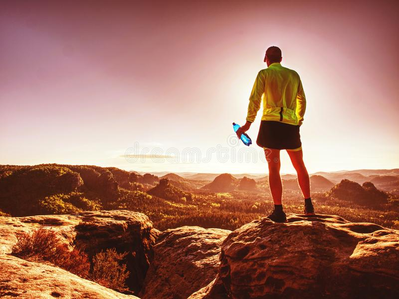 Geschikte agent die in sportkostuum het water van sportfles drinken stock afbeelding