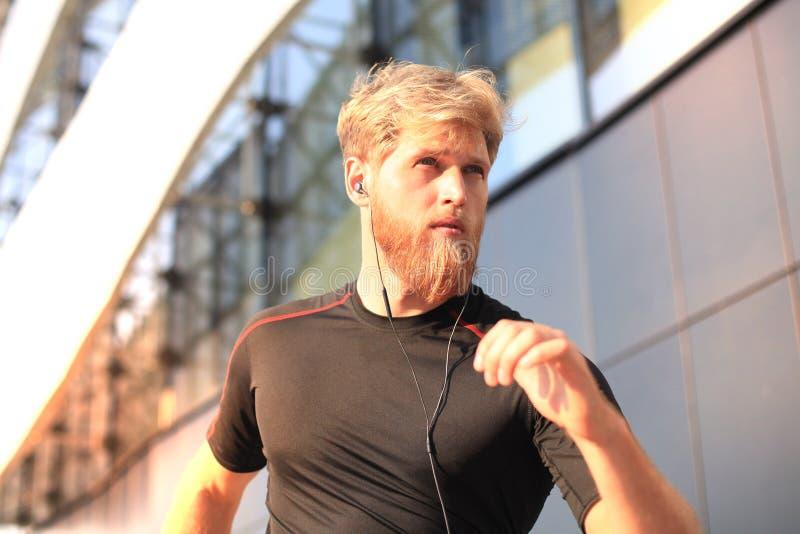 Geschikte atleet Knappe volwassen mens die in openlucht gezond, bij zonsondergang of zonsopgang lopen te blijven agent royalty-vrije stock foto